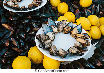 A lot of mussels with lemon on a plate. Sea food.