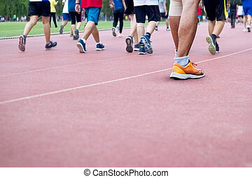 a lot of people walk excercise on runing track background, blank text