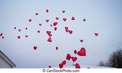A lot of red heart balloons in the air