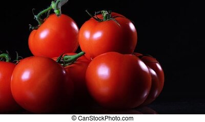 A lot of ripe fresh tomato lying on a black glass table and rotates around its axis. Close-up fresh vegetables.