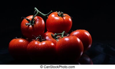 A lot of ripe fresh tomato lying on a black glass table and...