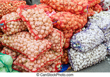 A lot of sacks full of garlic and onions.