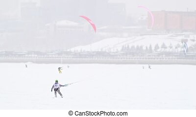 A lot of snow-kite sportsmen's rides on the ice river - winter extremal sport at blizzard