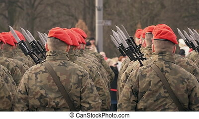 A lot of soldiers in red berets and green uniform stand with...