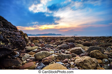 stone on the beach with sunset background.