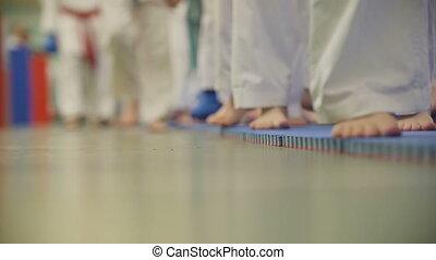 A lot of teenagers karatekas in white kimono going on tatami...