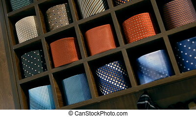 A lot of ties are lying folded on the shelves