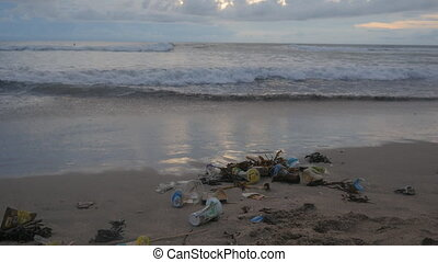 A lot of trash and plastic wastes on ocean beach after the...