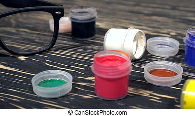 A lot of varicolored paint gouache jars with brushes on...
