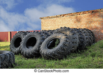 A lot of very large wheels lie near the brick wall.