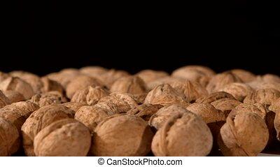A lot of walnuts, on black, rotation