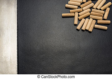 A lot of wooden pegs and hand saw for wood lying flat on a black background.