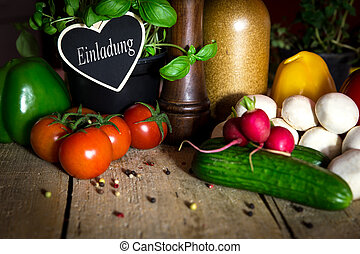 a lots of healthy vegetables on a wooden table, heart with word einladung