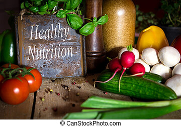 a lots of healthy vegetables on a wooden table, sign with text healthy nutrition