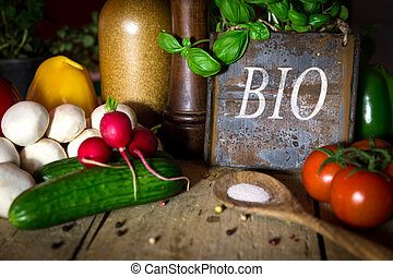 a lots of healthy vegetables on a wooden table, sign with word Bio
