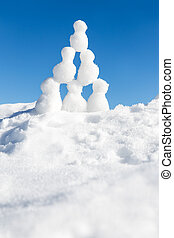 a lots of snow figures building a pyramid in the snow