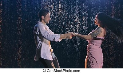 A love story of a happy couple dancing against the background of rain drops illuminated by blue light. Dance as a symbol of a strong passionate relationship between a man and a woman. Close up. Slow motion.