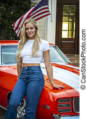 A Lovely Blonde Model Poses With An American Muscle Car In Front Of An Estate