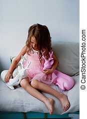 A lovely little girl 4 years old in a pink dress plays with pink deer. The atmosphere of childhood