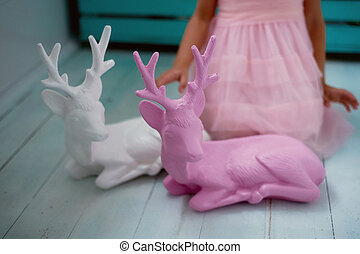 A lovely little girl 4 years old in a pink dress plays with pink deer.The atmosphere of childhood