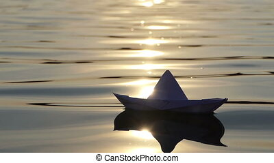 A lovely paper boat floats in a forest lake at sunset in slo-mo