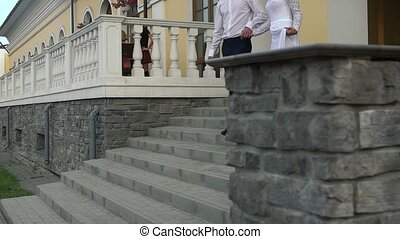 A loving couple coming out of the restaurant derzhast hands, go down the stairs on their wedding day.