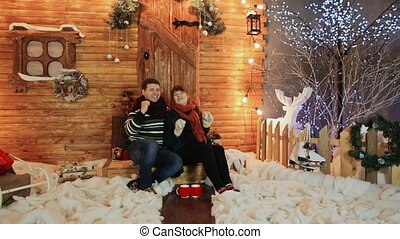 A loving couple dances sitting on the porch of a wooden fairy-tale house. Christmas and New Year theme.