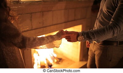 A loving couple dines by candlelight near the fireplace -...