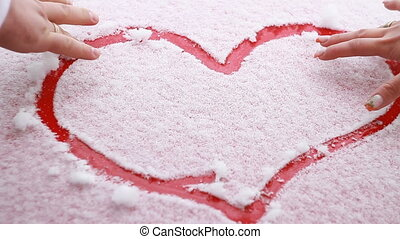 A loving couple draw a heart in the snow - Hand in the glove...
