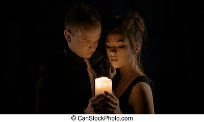 A loving couple, holding a candle, tenderly looking at each other. Valentine's Day.