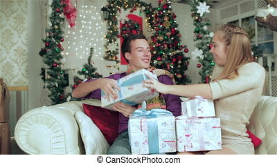 A loving couple holding Christmas presents