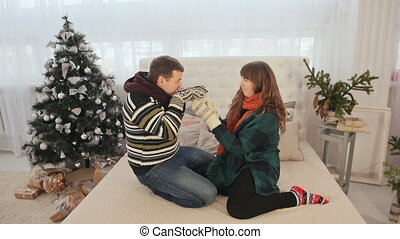A loving couple is having fun and dancing on the bed. Christmas Eve. Warm New Year's atmosphere.