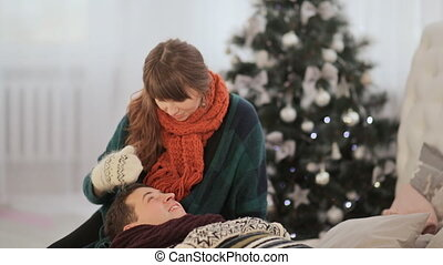 A loving couple is resting on the bed and a girl is stroking her boyfriend on the head. Warm Christmas Eve.