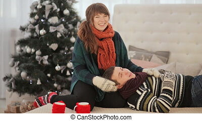 A loving couple is resting on the bed and showing the viewer the thumbs up. Good mood. Warm Christmas Eve.