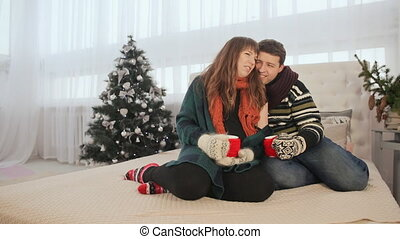 A loving couple is sitting on the bed and being warmed enjoying each other. They drink hot coffee. Christmas Eve. Warm New Year's atmosphere.