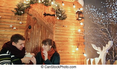 A loving couple is sitting on the porch of a wooden fairy-tale house. The guy dresses his favorite mittens and kisses her hands. Christmas and New Year theme.