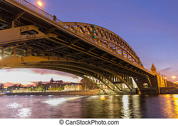 A loving couple is standing on a bridge over the river of the evening city.