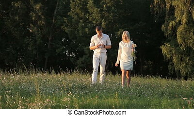 A loving couple is walking along the lawn