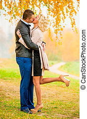 a loving couple kissing in autumn park
