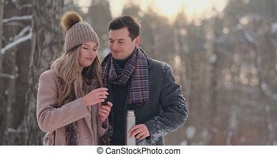 A loving couple man and woman in the winter forest drinking...