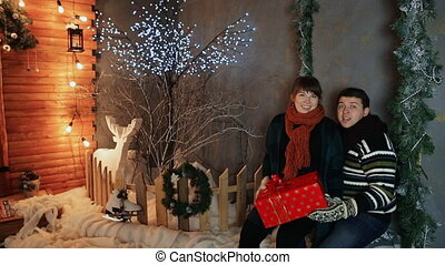 A loving couple playfully and amusingly gives the viewer a red gift against the backdrop of fairytale decorations. Christmas and New Year theme.