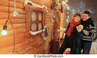 A loving couple sit on the background of a wooden fairy house dance funny. Christmas and New Year theme.