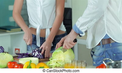 A loving couple sliced vegetables and smiling directly at the camera