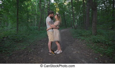 A loving couple standing in the woods and embraces.