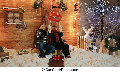 A loving couple toss a red gift on the porch of a wooden fairy-tale house. Christmas and New Year theme.