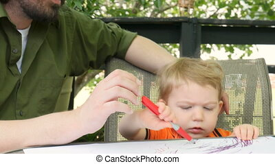 A loving father kisses his young toddler son while he draws on paper outside