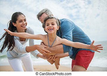 A loving six year old playing with mom and dad at the beach