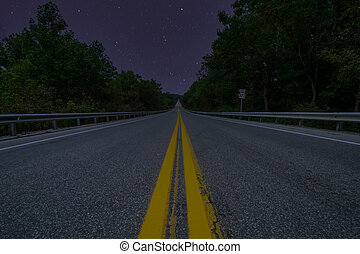 A Low Angle Shot of a Road at Night With Stars in the Sky