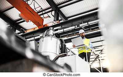 A low angle view of an industrial man engineer with laptop in a factory, working.