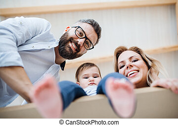 A low-angle view of young family with a toddler girl moving in new home.